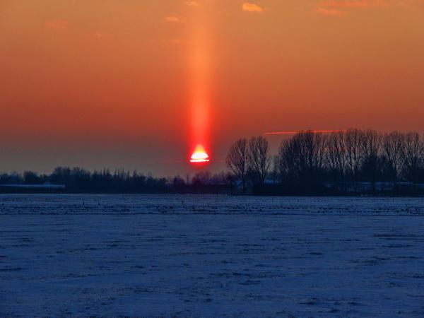 Een mooie lichtzuil is zichtbaar boven de ondergaande zon in Oostwoud (foto genomen door Frank Pereboom op 3 februari ±17:20).