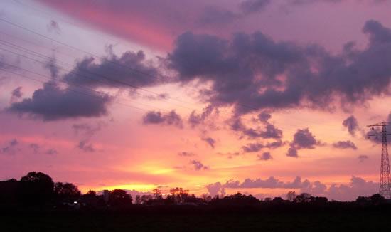 Tjeerd de Groot maakte deze foto in 2004 van het kleurenspel bij een ondergaande zon aan de Leeuwarderweg in Scharnegoutum.