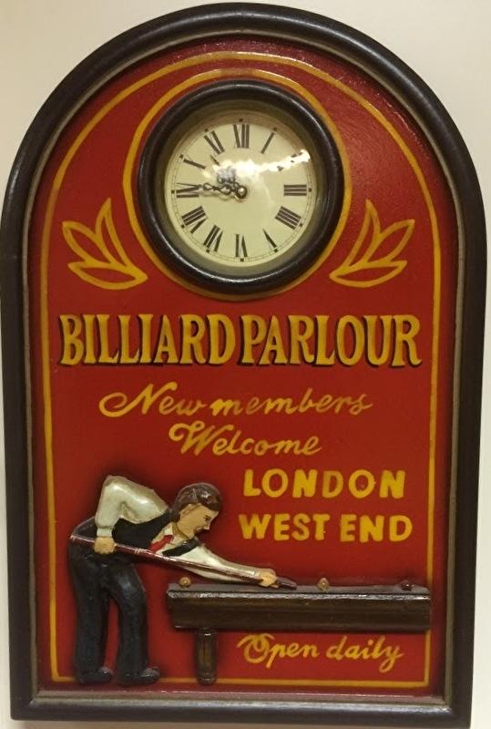 Een wandbord met biljarttafereel en ingebouwde klok.