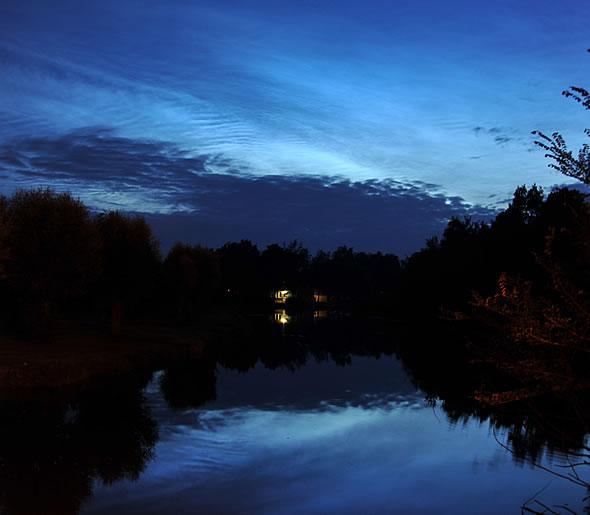 De prachtige lichtende nachtwolken van 14 juli 2009. De donkere vlekken op de voorgrond zijn lokale wolken en vandaar donker (foto Peter van Bommel).