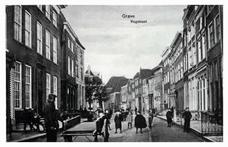 De Maasstraat zet zich voort in de Rogstraat, die altijd de voornaamste straat van het stadje is geweest. Helemaal links staat de r.k. pastorie, in 1803 door bisschop van Velde de Melroy aangekocht als residentie voor zijn miniatuurbisdom, bestaande uit de districten Nijmegen, Grave of Cuijk, en Druten van het voormalige bisdom Roermond. Het paleis werd in 1838 aan het Graafse kerkbestuur overgedragen.
