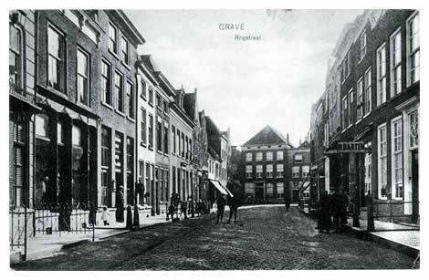 """De Rogstraat dankt zijn naam aan de graanmarkt, die vooral in de 18e eeuw bloeide. Paaltjes en stoepen, waarvan velen bestaan uit oude grafzerken, bepalen het straatbeeld. In het grote huis links heeft jarenlang de wijnkopers- en apothekersfamilie Walter gewoond. Op de achtergrond op het kruispunt Rogstraat - Brugstraat - Klinkerstraat en indirect Hamstraat staat het huis """"de Gouden Kop""""."""