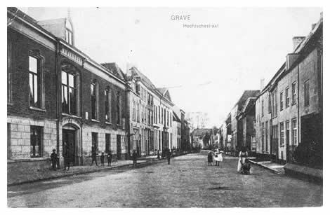 """Vanuit het straatje Kastele kunnen we de hele Hoofsestraat overzien met op het eind het klooster van de Franse paters. Links ligt de sociëteit """"tot Nut en de Vermaak"""", die in 1788 opgericht werd. Het huidige gebouw werd in 1841 aangekocht. Bij de lantaarn is de toegang tot het Trompetterstraatje, na een paar huizen komt dan de Bank van Lening, waar later de paters van de Heilige Harten hun intrek namen."""