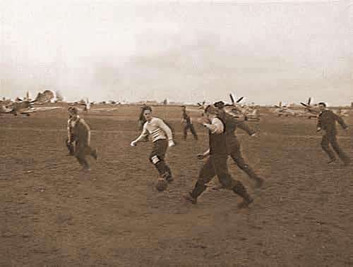 Australische en Engelse piloten en grondpersoneel van 130 (Punjab) Squadron spelen een ontspannend partijtje voetbal op de voorgrond van een indruk- wekkend rijtje Spitfires. (Foto is genomen op 23 oktober 1944).