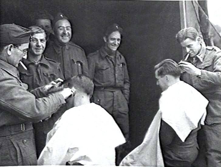 """""""Get yer 'air cut!!"""", zelfs tijdens de traumatische dagen op B.82 gaat het leven gewoon door als grondpersoneel - tussen de starts en landingen van de squadrons door - in de rij staat om geknipt te worden. (Foto gemaakt op 23 oktober 1944)"""