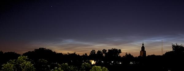 Een prachtige opname van lichtende nachtwolken boven de skyline van Zutphen. Deze wolken van fijnstof bevinden zich op een hoogte van ± 85 km. boven het zuiden van Scandinavië, waar ze nog worden beschenen door de zon - vandaar lichtende nachtwolken (foto gemaakt door Willem Bentink uit Zutphen om 0.26 uur op 2 juli 2012)
